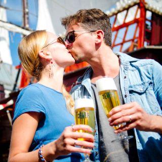 Pärchen küsst sich vor einem Schiff