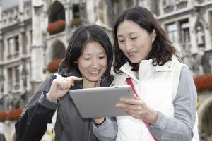 M-WLAN Marienplatz: Zwei asiatische Frauen mit Tablet vor dem Neuen Rathaus, Foto: SWM