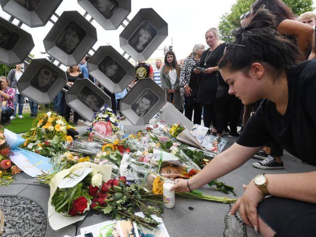 Besucher legen am Ende einer Gedenkveranstaltung Blumen am Denkmal nieder., Foto: dpa