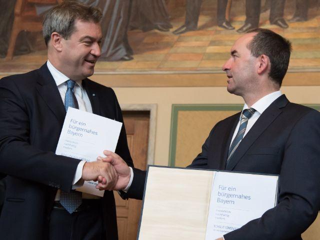 Maskus Söder und Hubert Aiwanger mit dem Koalitionsvertrag, Foto: dpa/Sven Hoppe