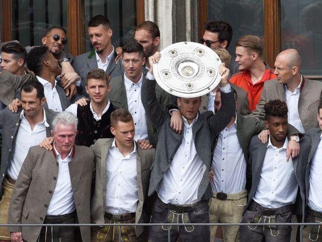 Die Mannschaft des FC Bayern München mit Torwart Manuel Neuer hält bei der Meisterfeier auf dem Rathausbalkon die Meisterschale in der Hand., Foto: dpa