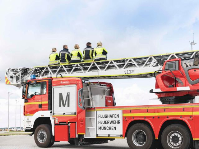 Feuerwehrmänner auf ihrem Einsatzfahrzeug, Foto: Flughafen München