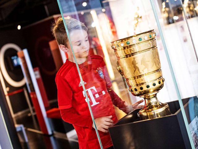 Kind im Bayern-Trikot vor Pokal
