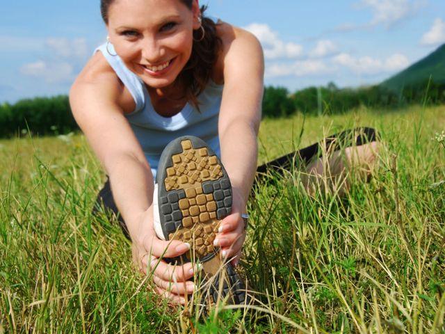 Frau dehnt sich im Gras