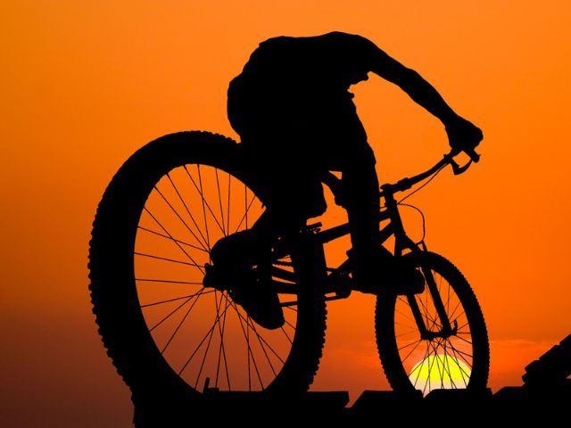 Mann auf Mountainbike im Abendrot, Foto: Shutterstock