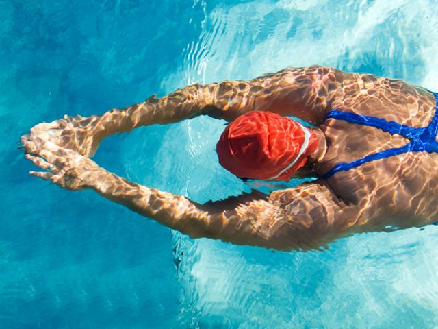 Frau in Badeanzug und Schwimmbrille taucht im Schwimmbecken