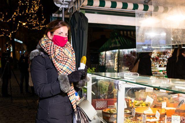 Kristina Frank, Kommunalreferentin, isst eine saure Gurke auf dem Viktualienmarkt