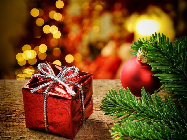 Weihnachtsgeschenk neben Tannenzweig, Foto: Symbiot / Shutterstock.com