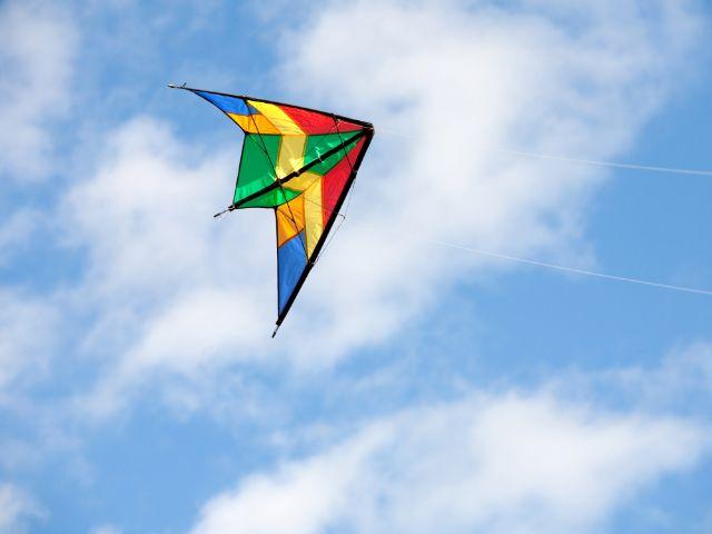 Drache fliegt vor blauem Himmel, Foto: Gelpi JM / Shutterstock.com