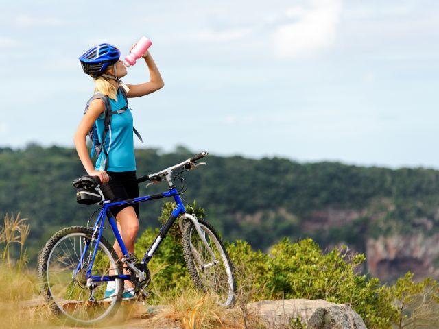 Frau mit Mountainbike auf Berg, Foto: Warren Goldswain / Shutterstock.com
