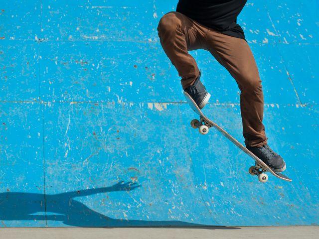 Skateboarder macht Kickflip vor blauer Wand, Foto: pio3 / Shutterstock.com