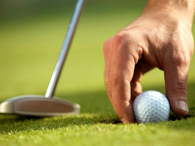 Golfspieler positioniert den Ball auf dem Grün, Foto: Prod-akszyn / Shutterstock