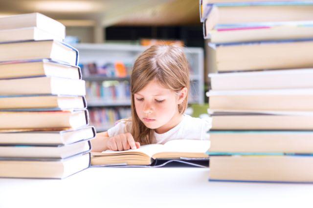 Kind zwischen Bücherstapeln in Lektüre vertieft