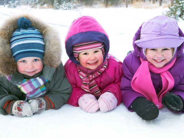 drei Kinder dick angezogen im Schnee, Foto: YanLev / Shutterstock