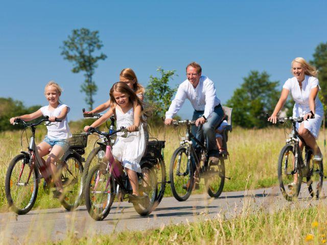 Familie macht einen Fahrradausflug in der Sonne, Foto: Kzenon/Shutterstock.com