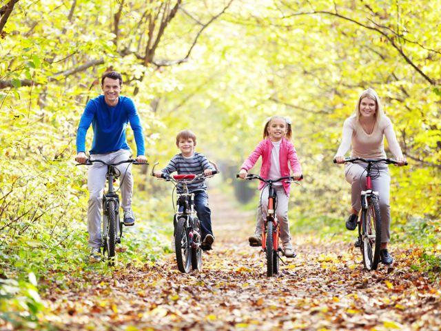 Familie radelt durch Herbstwald