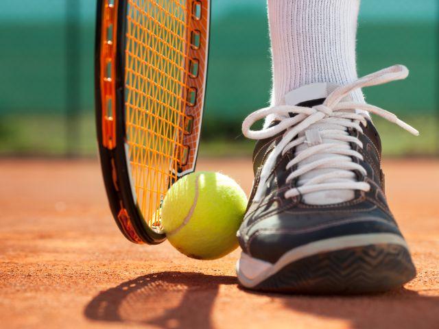 Tennisball zwischen Schuh und Schläger, Foto: Lucky Business / Shutterstock.com