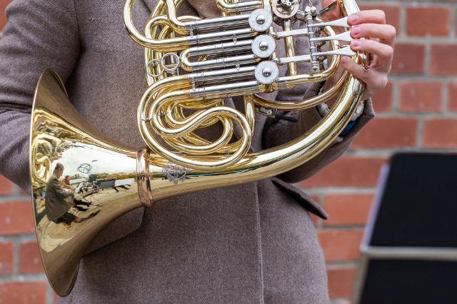 Die Richtkrone spiegelt sich im Instrument eines Münchner Philharmonikers, Foto: Anette Göttlicher