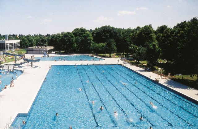 The spacious pools of the Michaeli-Freibad surrounded by large trees., Foto: SWM
