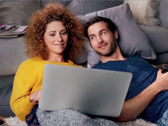 Mann und Frau vor einer Couch auf dem Boden mit Laptop, Foto: SWM