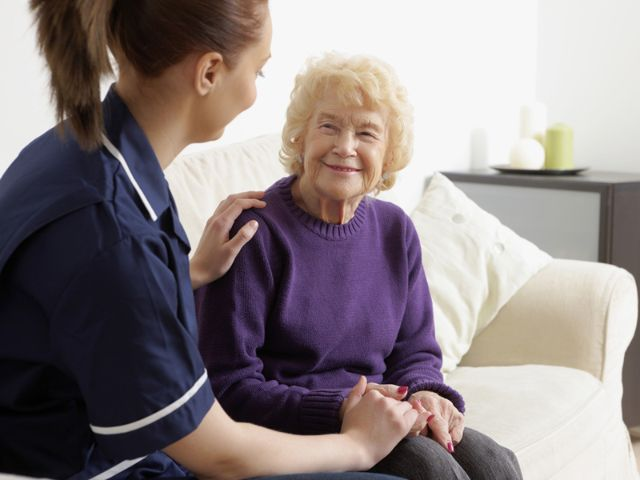 Krankenschwester mit Seniorin auf dem Sofa
