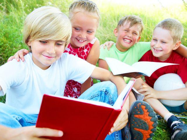 Kinder mit Buch im Gras, Foto: YanLev/Shutterstock.com
