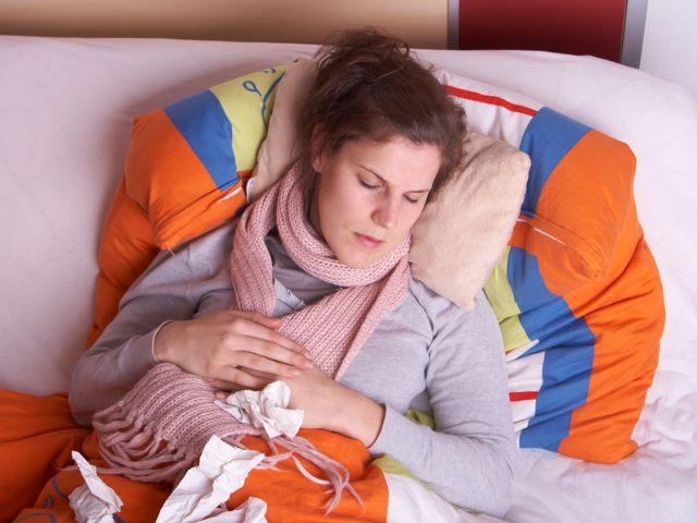 Frau mit Grippe liegt im Bett