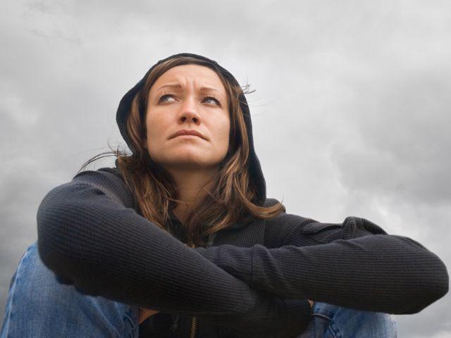 Frau mit Sorgesfalten vor grauem Himmel