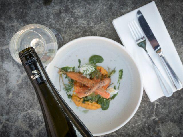Gedeckter Tisch mit einem Gericht und Wein, Foto: Regionales Weinkomitee Weinviertel / Astrid Bartl