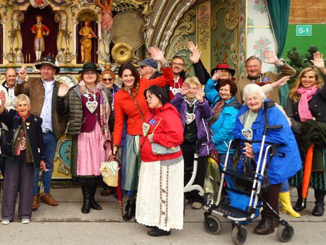Natalie Schmid und einige der Gruppe von Senioren winken beim Rundgang über Wiesn. , Foto: muenchen.de/ Daniel Vauel