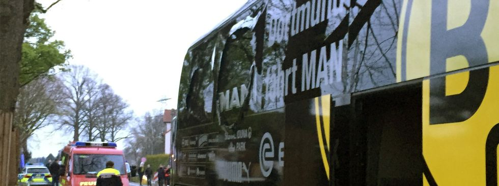 Der Bus von Borussia Dortmund steht mit einer beschädigten Scheibe in Dortmund an einer Straße. , Foto: dpa