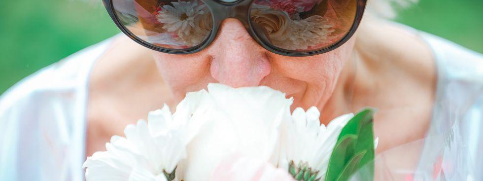 Ältere Frau schnuppert an Blumen