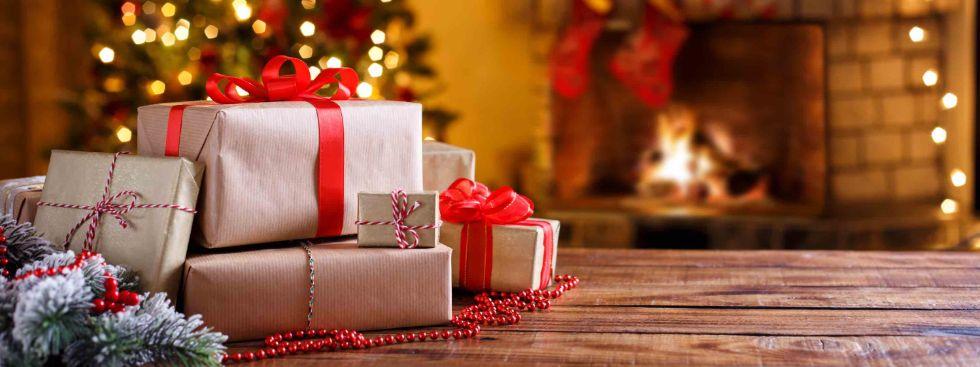 Geschenke auf einem Holztisch vor Christbaum und Kamin, Foto: Shutterstock/Lucky_7