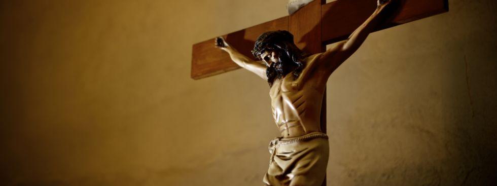 Eine Jesusfigur hängt an einem Holzkreuz., Foto: Diego Cervo / Shutterstock.com