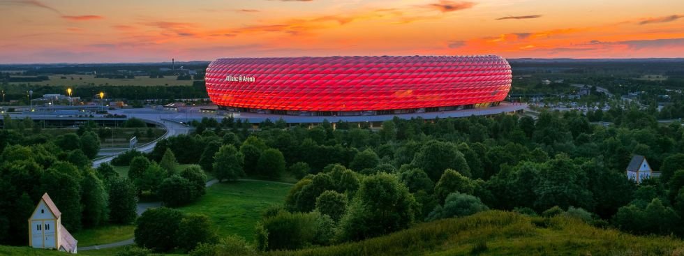 Die rot beleuchtete Allianz Arena in der Dämmerung