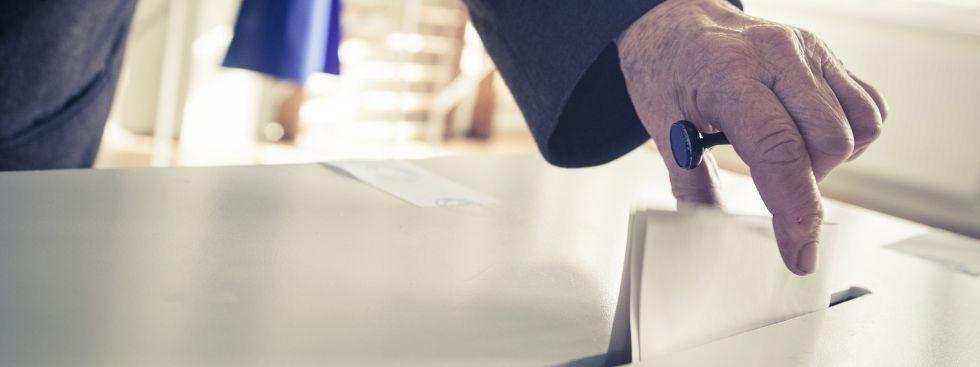 Mann wirft Zettel in Wahlurne