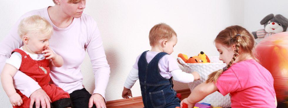 Kinder spielen unter der Aufsicht einer Frau