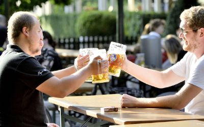 Männer stoßen im Biergarten an