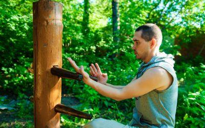 Mann trainiert Wing Tsun an Holzpfosten