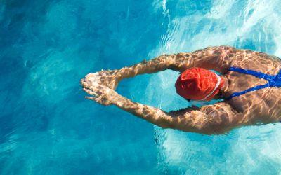 Frau schwimmt mit Badekappe im Schwimmbad.