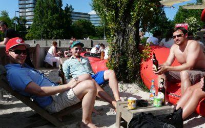 Junge Männer entspannen in den Liegestühlen des Kulturstrandes München.