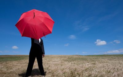 Mann im Anzug unter rotem Regenschirm und blauem Himmel