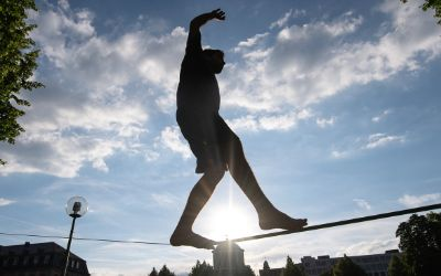 Ein Sportler balanciert auf einer Slackline.