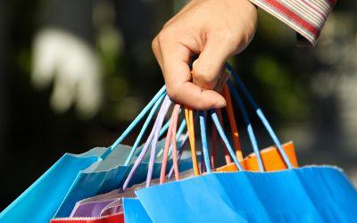 Hand mit bunten Einkaufstüten