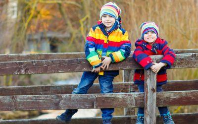 Kinder im Winter auf einer Holzbrücke