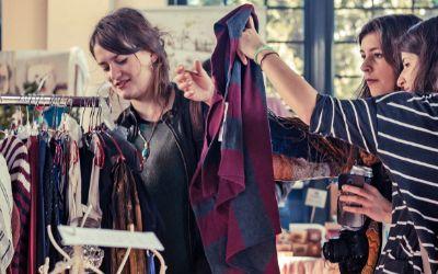 Frauen durchstöbern Klamotten auf einem Flohmarkt