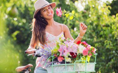 Eine Frau auf dem Fahrrad mit Blumen im Korb