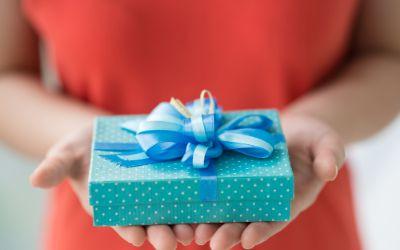 Detailansicht einer Frau, die ein Geschenk vor sich in den Händen hält