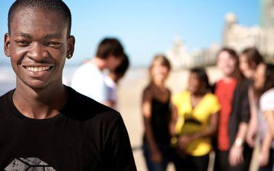 Junger Afrikaner vor Gruppe anderer Jugendlicher