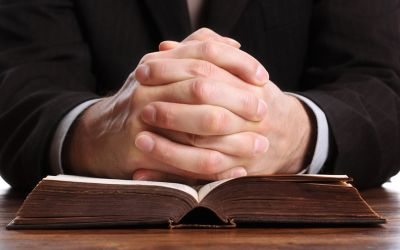 Priester faltet die Hände über Bibel zum Gebet